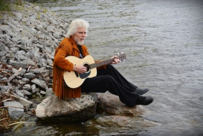 Kenny Butterill playing music on a rock